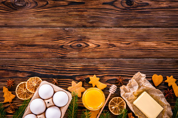 Traditional christmas holidays pastry ingredients and various kitchen utensils on wood textured table. Ginger cookies recipe concept. Close up, copy space, top view, flat lay, background.