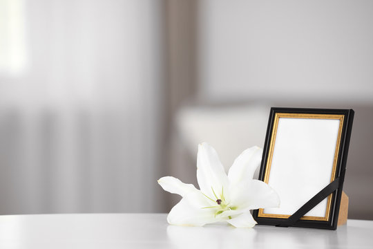 Funeral photo frame with black ribbon and lily on white table indoors. Space for design