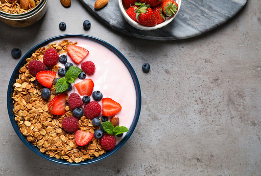 Healthy homemade granola with yogurt on grey table, flat lay. Space for text