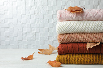 Fototapete - Stack of warm clothes and autumn leaves on white wooden table against textured wall. Space for text