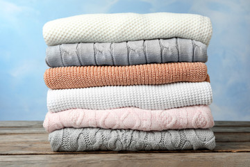 Fototapete - Stack of warm clothes on wooden table against light blue background. Autumn season
