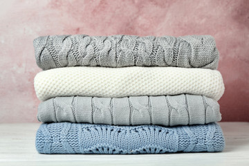 Stack of warm clothes on white wooden table against light background. Autumn season