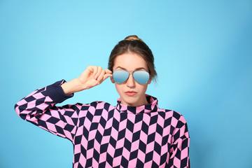 Young woman wearing stylish sunglasses on blue background