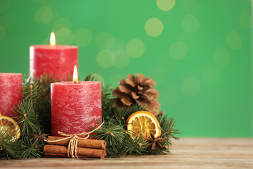 Beautiful Christmas composition with burning candles on table against green background. Space for text