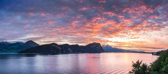 Bright sunset painted the sky red. Switzerland, Alps and Lake Lucerne.