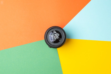 one broken modern photo lens on a colored background, photographic equipment repair concept Wall mural