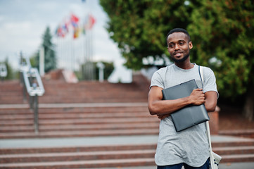 African student male posed with backpack and school items on yard of university, against flags of different countries.
