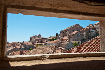 Dubrovnik, Croatia: view through a small window in the city wall to the roofs of the old town