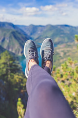 Woman hiker legs with sports shoes against beautiful valley and hills in the background. Healthy lifestyle and nature concepts.