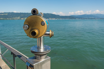 Coin operated binoculars with lake view on touristic promenade.