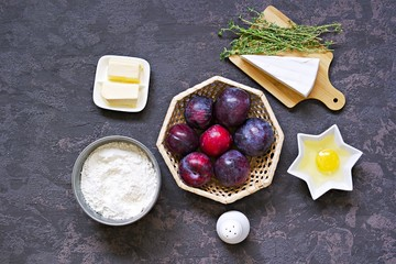 Ingredients for cooking unsweetened shortcrust pastry pie with plums, brie cheese and thyme. Top view. Plum recipies.