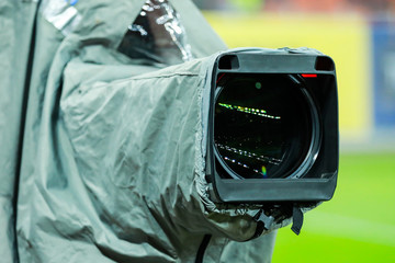 Details of a professional television camera, with rain cover, live broadcasting a soccer game.