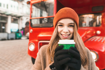 Printed roller blinds London red bus Closeup portrait of happy girl with cup of coffee standing against red bus background, looking into camera and smiling. Street photo of cheerful girl on a walk in winter, warmed by warm coffee.
