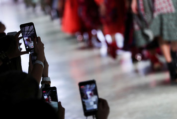 Models present creations from Fernanda Yamamoto as people take pictures with their cell phones during Sao Paulo Fashion Week, in Sao Paulo