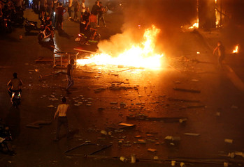 Demonstrators walk close to fire during a protest over deteriorating economic situation in Beirut