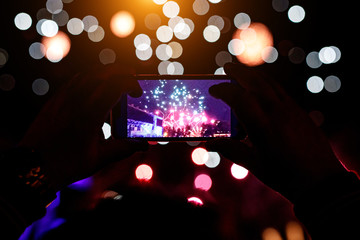 Hand of man taking the photo of fireworks by smartphone