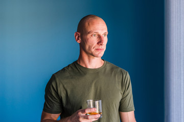 Portrait of young handsome man with short hair holding a glass of whiskey or brandy alcohol drink standing in front of blue wall looking trough the window