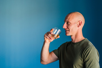 Portrait of young handsome man with short hair holding a glass of whiskey or brandy alcohol drink standing in front of blue wall side view profile