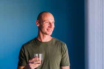 Portrait of young handsome man with short hair holding a glass of whiskey or brandy alcohol drink standing in front of blue wall looking trough the window smiling