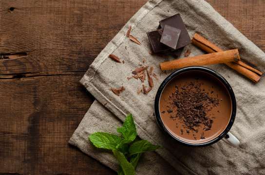 cup of hot chocolate, cinnamon sticks, mint and chocolate on wooden table