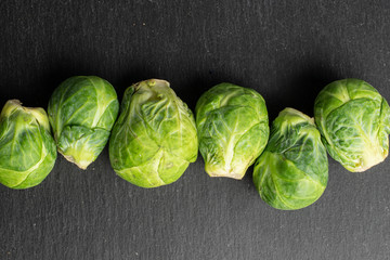 Group of six whole fresh green brussels sprout flatlay on grey stone