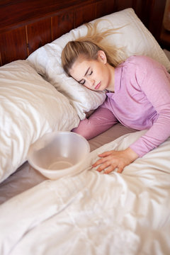 Feeling dizzy and sick in bed, unwell female