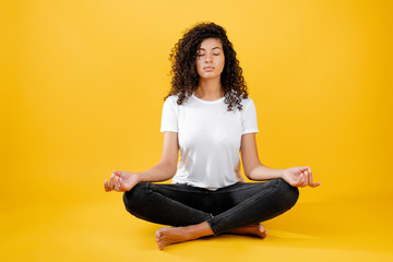 Photo sur Plexiglas Ecole de Yoga relaxed black woman meditating in yoga pose isolated over yellow