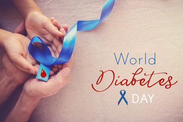 adult and child hands holding Blue ribbon, world diabetes day