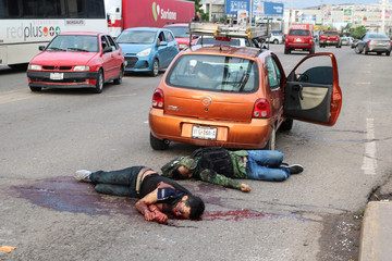 """Dead bodies lie next to a car during clashes between Cartel gunmen and federal forces following the detention of Ovidio Guzman, son of drug kingpin Joaquin """"El Chapo"""" Guzman, in Culiacan"""