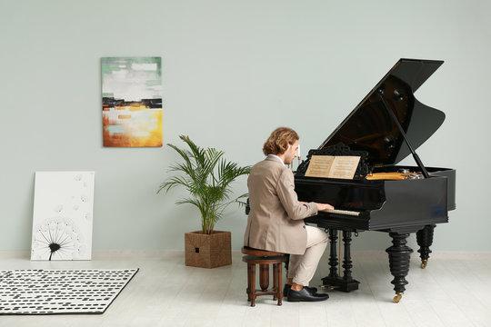 Man playing grand piano at home