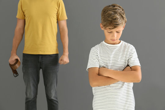 Man threatening his little son against grey background. Physical punishment concept