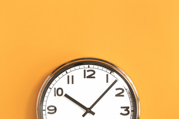 Part of analogue plain wall clock on trendy pastel orange background. Ten o'clock. Close up with copy space, time management or school concept and summer or winter time change