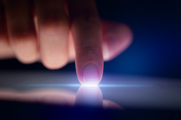 Finger touching tablet with dark background with copyspace