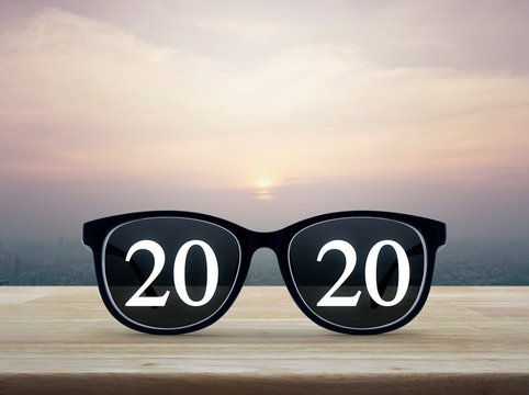 2020 white text with black eye glasses on wooden table over city tower and skyscraper at sunset, vintage style, Business vision happy new year 2020 concept