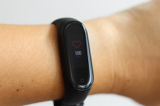 Close-up portrait of sport girl using fitness tracker or heart rate monitor