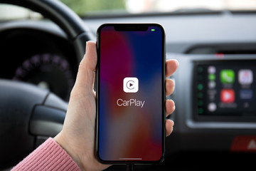 Woman hand holding iPhone X with CarPlay in car.