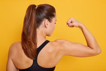 Horizontal shot of attractive fitness woman posing backwards isolated over yellow studio background. Trained female body, girl showing her biceps, lady with ponitail wearing black sport top.