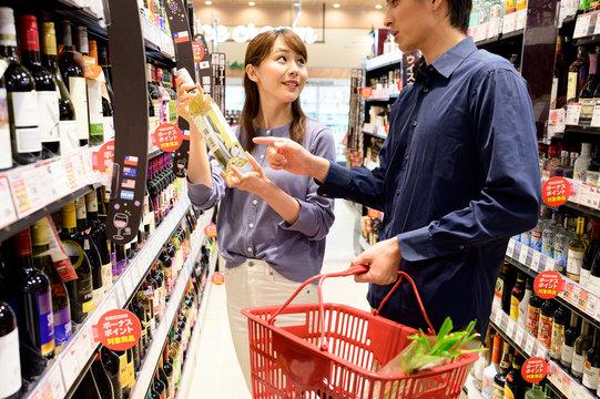 どのワインを買うか相談するカップル