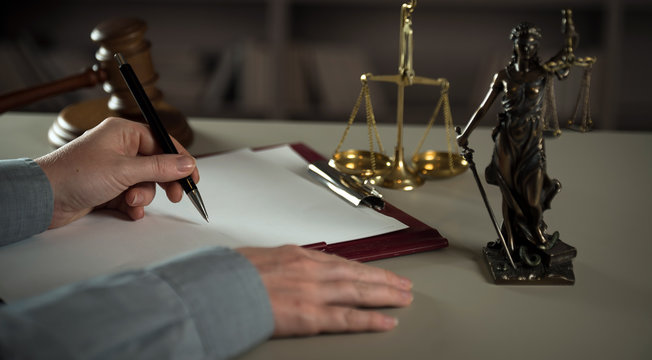 A lawyer working at a desk in a courtroom
