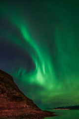 Fond de hotte en verre imprimé Aurore polaire Green aurora borealis on dark night sky with stars. In foreground edge of a mountain and in background the ocean and part of an island. At Tromso, Norway. Northern lights over ocean.