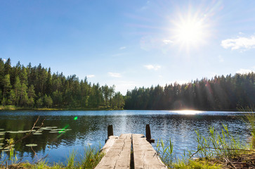 Foto op Plexiglas Noord Europa Traditional Finnish and Scandinavian view. Beautiful lake on a summer day and an old rustic wooden dock or pier in Finland. Sun shining on forest and woods in blue sky.