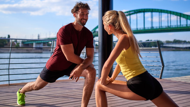 Modern woman and man exercising in urban surroundings near the river.
