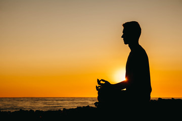 In de dag Ontspanning Silhouette of a man in meditation pose on beach on sea background and sunset. Concept of freedom relaxation. Place for text or advertising