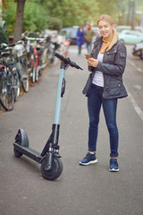 Young blond woman standing near electric kick scooter on city street or park, with bicycles parked on the side. Holding phone in her hands and smiling. Urban transportation renting