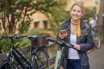 Happy young woman in casual grey jacket looking at camera and smiling, standing in the street with an e-scooter with mobile phone in her hands.