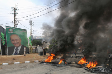 A picture of parliament speaker Nabih Berri is seen near burning tires during a protest targeting the government over an economic crisis, in Nabatiyeh