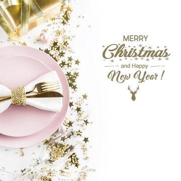 Christmas table setting with pink dishware, golden silverware and party decorations on white background. Top view. Xmas invitation.