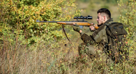 Man wear camouflage clothes nature background. Hunting permit. Hunting equipment for professionals. Hunting is brutal masculine hobby. Bearded serious hunter spend leisure hunting. Hunter hold rifle