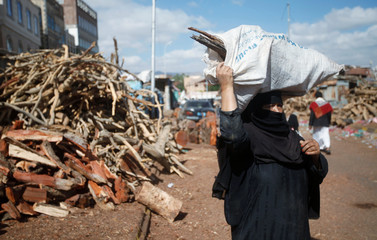 Woman carries a bag of wood poles at a market amid the ongoing fuel and cooking gas shortages in Sanaa