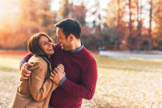 Happy couple at public park in autumn